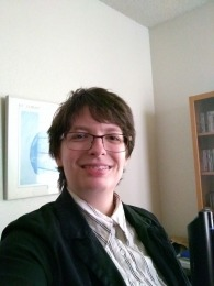 Asa, a genderqueer person with glasses and short hair, smiles at the camera.