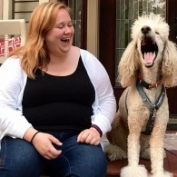 Anna laughs staring at Wes, her poodle service dog, whose mouth is wide open.